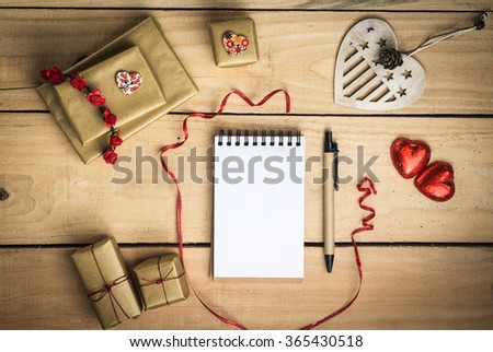 Valentines day card concept with copy space for a note. Wooden and red hearts, gift boxes for a present. Curved ribbon.  - stock photo