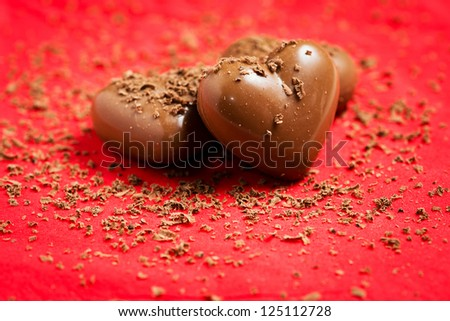 Valentines day card - sweet chocolate hearts on red background - stock photo