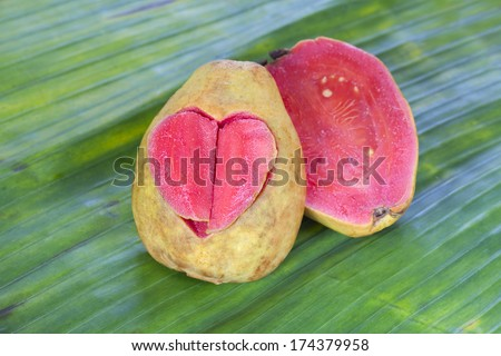 Valentines day card. Two halves pink guava with carved heart on green leaf background - stock photo