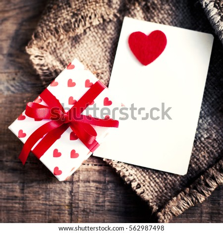 Valentines day Card with gift boxes and  hearts, blank white card for messaage  and red hearts on dark wooden background
