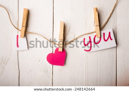 Valentines day card with hearts and words of love on old wood background