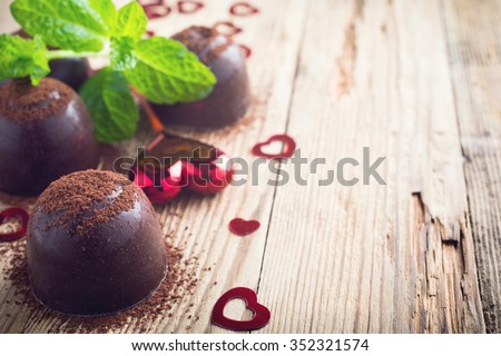 Valentines day composition with chocolate candies and hearts on vintage wooden background. Toned photo with copy space for text. - stock photo