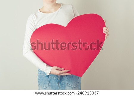 Valentines Day Concept - young adult caucasian woman holding big red heart shaped paper.
