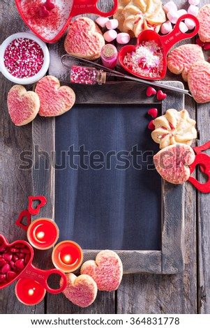 Valentines day cookies and decorations around a chalkboard copy space - stock photo