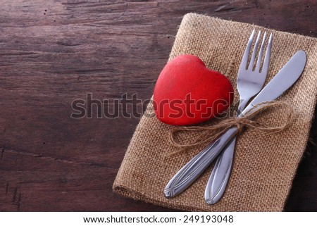 Valentines day dinner. Seasonal old dark table with cutlery and heart. - stock photo
