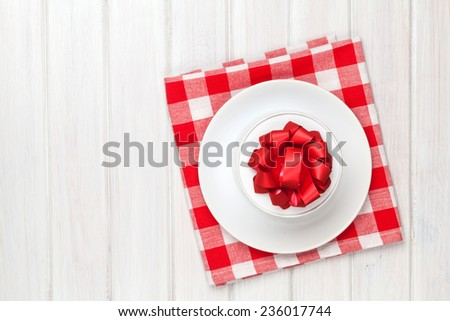 Valentines day gift box on plate over white wooden table background with copy space - stock photo