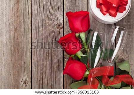 Valentines day gift box, red roses and champagne glasses on wooden table. Top view with copy space - stock photo