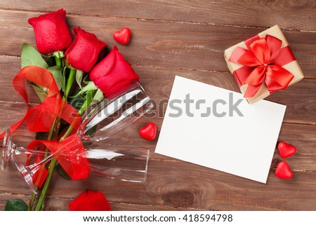 Valentines day greeting card, gift box and red roses on wooden table. Top view with copy space
