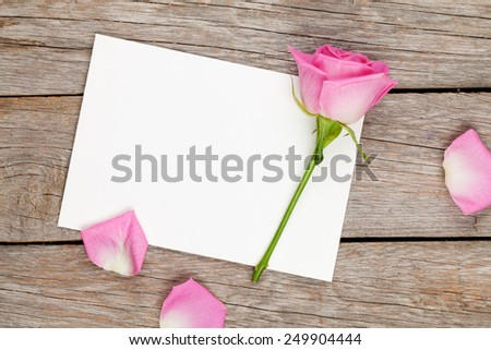 Valentines day greeting card or photo frame and pink rose over wooden table. Top view with copy space - stock photo