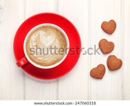 Valentines day heart shaped cookies and red coffee cup. View from above over white wooden table - stock photo