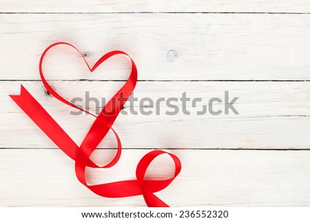 Valentines day heart shaped ribbon over white wooden table background with copy space