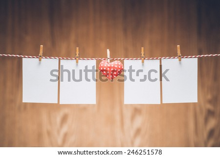 Valentines day heart with four blank photos hanging on the rope isolated on wooden background. Vintage color.   - stock photo