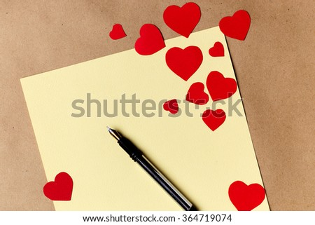 Valentines day letter writing on yellow paper with heart paper cut decoration - stock photo