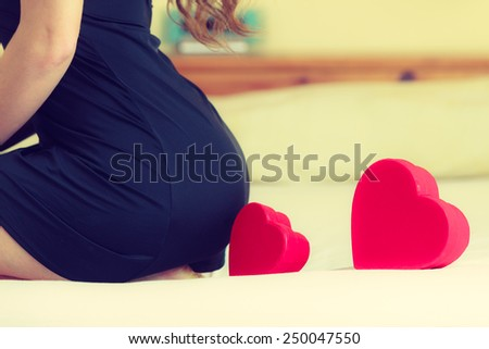 Valentines Day, love, feelings. Close up woman part body bottom in black lingerie dress on bed with red heart shaped box gift. Indoor. - stock photo