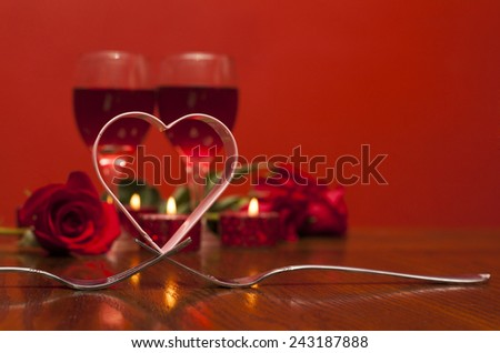 Valentines day: love heart on forks on the background of glasses of vine, red roses, candles  - stock photo