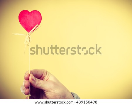 Valentines Day. Male hand holding showing red little heart on stick. Man presents palm with love sign symbol.