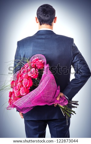 Valentines day. Man hiding behind a bouquet of flowers. Proposal scene - stock photo