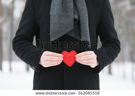 Valentines Day. Man with a red decorative heart - stock photo