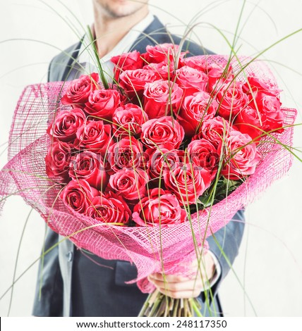 Valentines day or proposal. Young happy handsome man holding big bunch of red roses in his hand on grey background, studio shot - stock photo