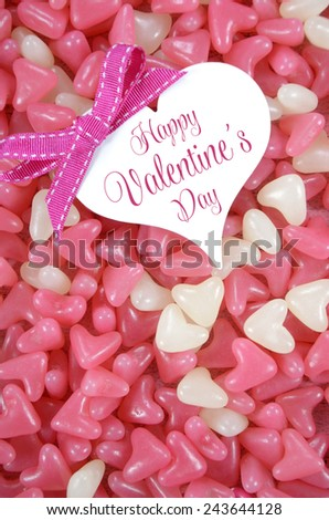 Valentines Day pink and white heart shape jelly candy confectionary on pink wood background with heart greeting card and sample text - vertical. - stock photo