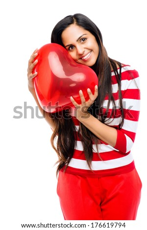 Valentines day portrait of Pretty Indian woman holding red heart balloon - stock photo