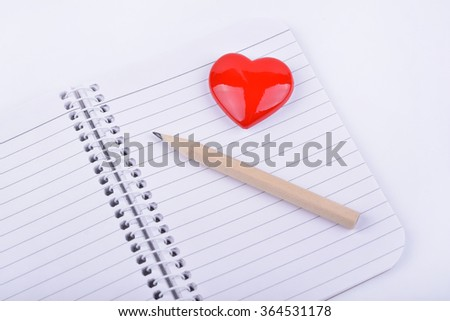 Valentines day red heart and pencil on opened notebook  - stock photo
