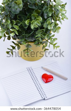 Valentines day red heart, notebook and green plant - stock photo