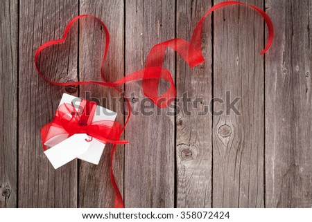 Valentines day ribbon heart and gift box on wooden table. Top view with copy space