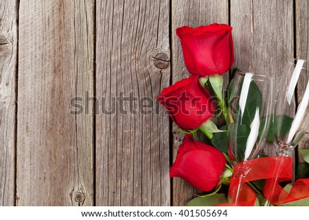 Valentines day roses bouquet and champagne glasses on wooden table. Top view with copy space - stock photo