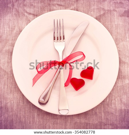 Valentines day set with silverware. Valentine day love beautiful. Romantic dinner, tableware and hearts on wooden background.Top view.