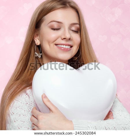 Valentines Day. Sweet blonde woman holding a balloon. heart  pink background Joyful - stock photo