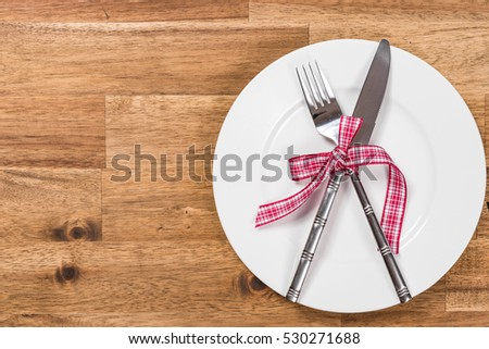 Valentines day table setting with plate, fork, knife and ribbon. Valentines day background