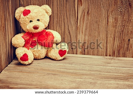 Valentines Day. Teddy Bear Loving with red hearts, Vintage. Retro Styled. Love concept on wooden background - stock photo