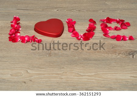 Valentines day. The word love spelled with rose petals and the o is replaced with a heart shape.
