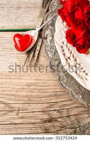 Valentines day themed table setting with heart and roses on a vintage plates on a shabby wooden background