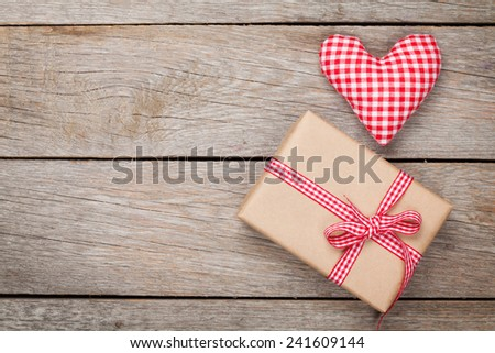 Valentines day toy heart and gift box over wooden table background - stock photo