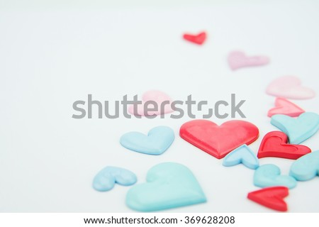 Valentines day wallpaper.Colorful, light pink, blue and red love hearts on white paper background. - stock photo