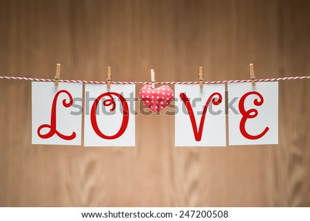 Valentines Day. Word Love dots, Heart Handmade, hanging on rope. Vintage style. Love concept on wooden background - stock photo