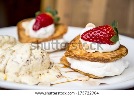 Valentines dessert. Almond mousse, strawberry and ice cream in a heart shape. - stock photo