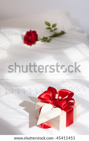 Valentines gift on bed in morning sunlight with rose on pillow