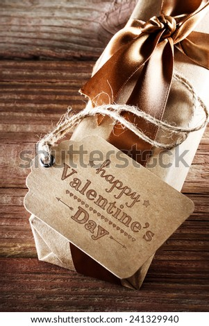 Valentines message with a present box with a brown ribbon on a rustic wooden table - stock photo