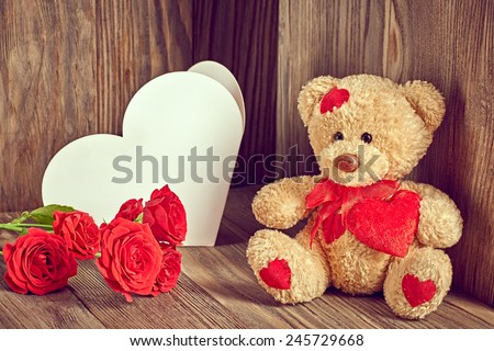 Valentines Teddy Bear Loving with Red Roses and greeting card. Vintage. Retro Styled. Love concept on wooden background - stock photo