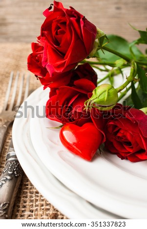 Valentines themed table setting with heart, roses on a silver and white china vintage plates