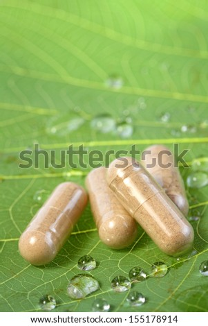 Valerian pills over a green leaf with water drops - stock photo