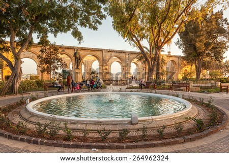 VALETTA, MALTA - JANUARY 18 2015: Locals and tourists in park with fountain in Upper Barrakka Gardens, Valetta, Malta