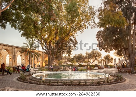 VALETTA, MALTA - JANUARY 18 2015: Locals and tourists in park with fountain in Upper Barrakka Gardens, Valetta, Malta - stock photo