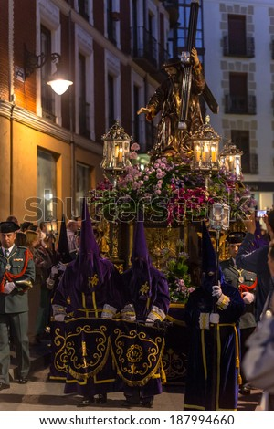 VALLADOLID, SPAIN - APRIL 18, 2014: Purple nazarenos carrying Jesuschrist sculpture in the religious processions during Holy Week on Good Friday Night, on April 18, 2014 in Valladolid, Spain.