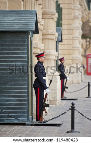 VALLETTA, MALTA - APRIL 4: Two sentries on guard duty stand outside of the Grand Masters Palace in Valletta, Malta on April 4, 2012. The palace is currently in use as the Presidential office.