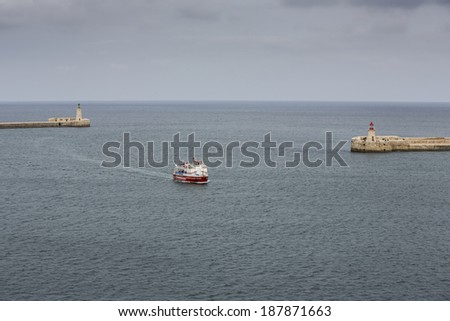 VALLETTA, MALTA - March 24: A ferry with tourists is entering the Grand Harbour on March 24, 2014 in Valletta, Malta. Boat rides are very popular among tourists in Malta.