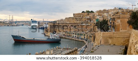 VALLETTA, MALTA - OCTOBER 30, 2015 : View of Valletta with ships and boats on coastline, on cloudy sky background.